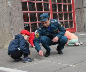 Пожарный и ребенок рисуют на асфальте